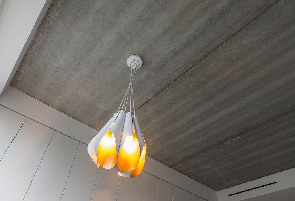 Šilto spektro auksinė lempa nuostabiai išryškėja industrinio betono fone. Interjero ir nuotraukų autorius Lukas Gadeikis.