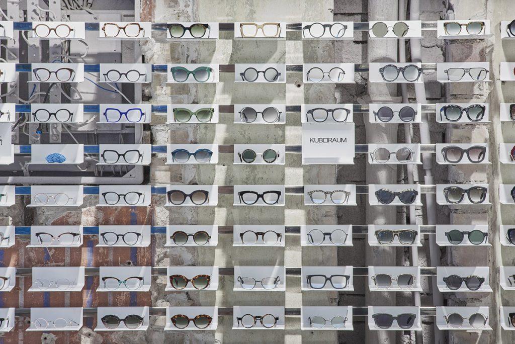 Maži skirtingi mėlyno metalo spalvos elementai užima tuščias vietas lentynėlėse, kai nėra akinių. Dariaus Petrulaičio nuotr.