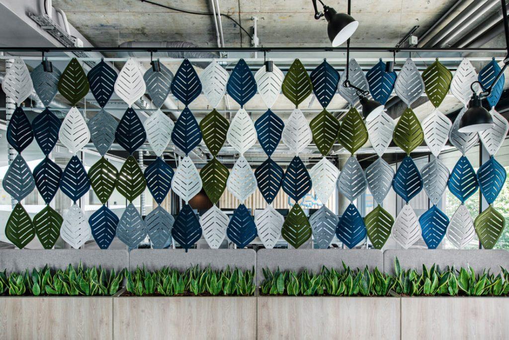Biurą puošia skirtingų raštų bei spalvų iš akustinio veltinio pagamintų medžio lapų sienelė. Leono Garbačausko nuotr.