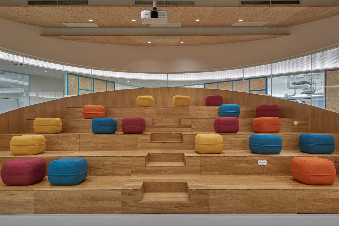Amfiteatras suformuotas iš medžio pakylų,ant kurių išdėlioti erdvę pagyvinantys spalvingi pufai. Dariaus Petrulaičio nuotr.
