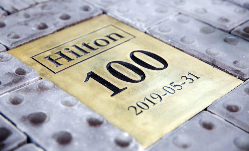 """Simbolinė """"Hilton Garden Inn"""" šimtmečio plytelė."""