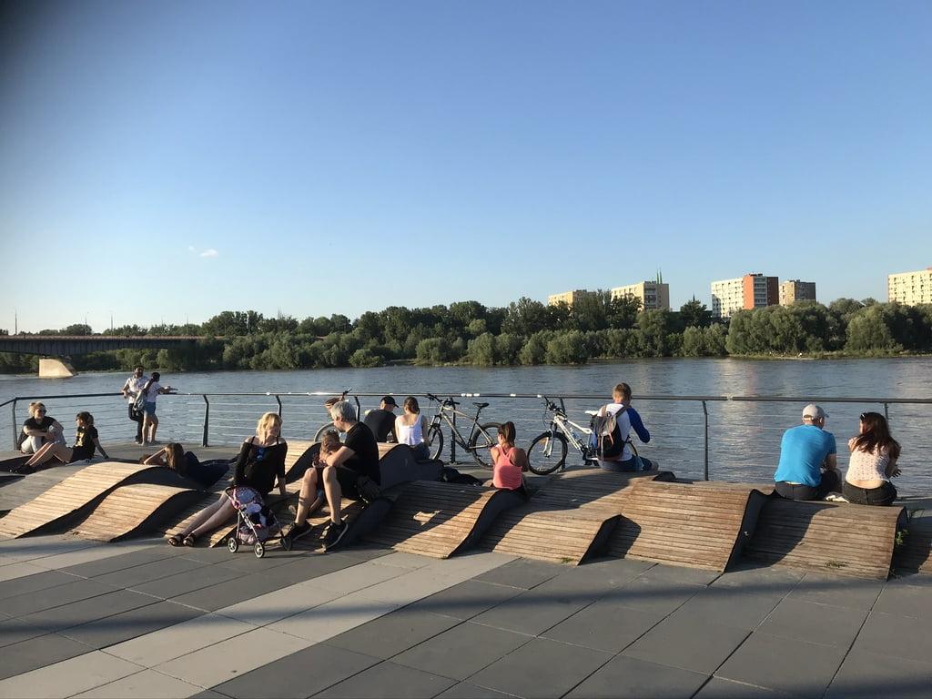 Kartu ir atskirai. Žvelgiant į miestą ir į upę. Prisėdus ar prigulus. Vienas iš daugelio sėdėjimo scenarijų pasiūlymų Vyslos krantinėje Varšuvoje.